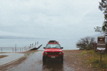 a red jeep cherokee parked by a boat ramp