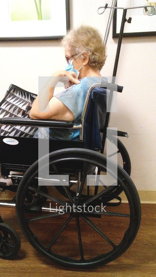 An elderly woman with white hair in a wheelchair wearing a face mask awaiting help from a Doctor or Nurse at a hospital. The year of Covid-19 has taken its toll on nursing homes across the country as CNA's, Nurses and health care professionals get sick from COVID-19 and endanger the lives of the elderly causing shutdowns, isolation, loneliness and separation from loved ones as well as a devastation to the United States Economy. While sickness, fear, poverty make headline news, people forget that the Lord is still in control over their lives, their wealth, their health and their eternal reward in Heaven. COVID-19 may be the buzzword for the year 2020 but it is not the final word on our future as Christ holds the future in His hands, even when we are old and gray.
