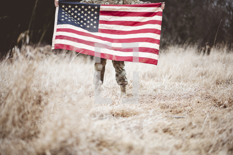 soldier in a field holding an American flag