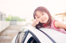 a little girl hanging out of a sunroof giving a peace sign