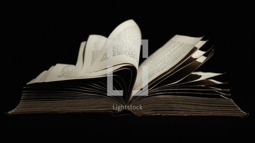 Old book open with pages turning isolated on black