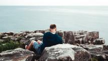 a man sitting on rocks along a shore