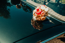 a bouquet of flowers on the hood of a car and bride and groom reflection