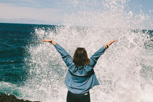 Woman with her arms raised as she faces the splash of the ocean water.