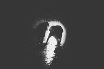 Silhouette of a couple walking through a wet drainage pipe.