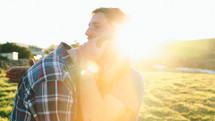 Sun shining on a man embracing and comforting another man.