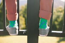 Feet standing on metal rails.
