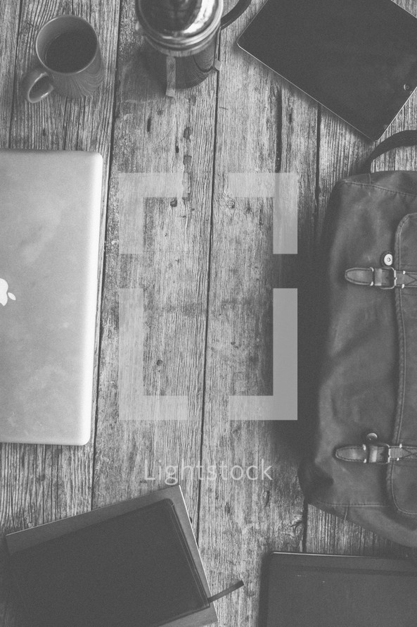 Laptop, bag, notebooks, Bible and coffee on a table