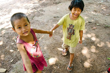 young children holding hands outdoors