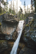 man jumping over a rock cliff and waterfall