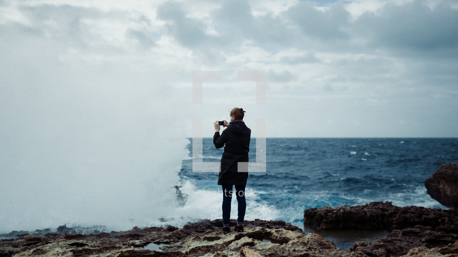 taking a picture standing on a rugged shore