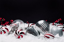 silver and red and white ornaments in snow