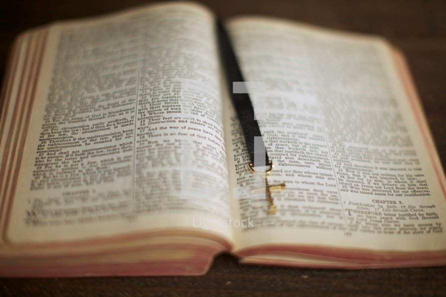 An open Bible with a cross bookmark down the middle