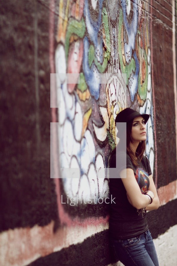 A teenage girl leans up against a brick graffiti wall with arms crossed