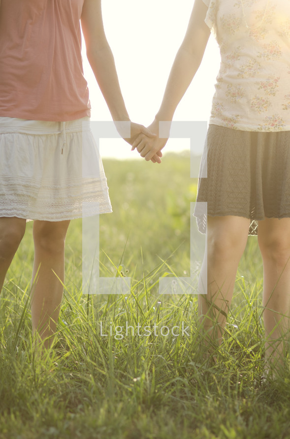 Sisters holding hands in the park