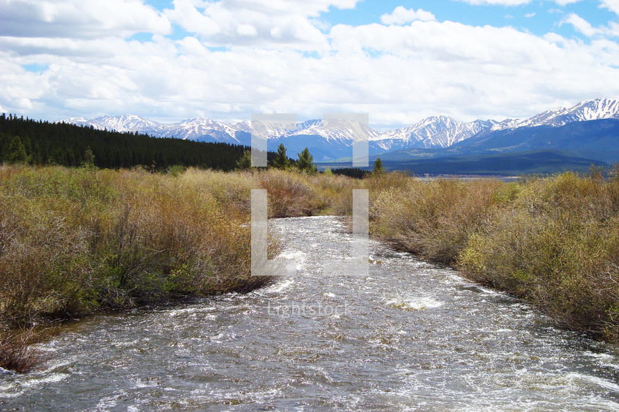 A river flowing through a field toward snow capped mountains with blue sky and clouds