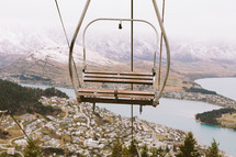 An empty ski lift chair in the air above a town.