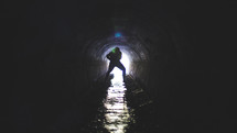 Silhouette of a man in a wet drainage pipe.