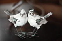 wedding bands on the heads of two bird sculptures