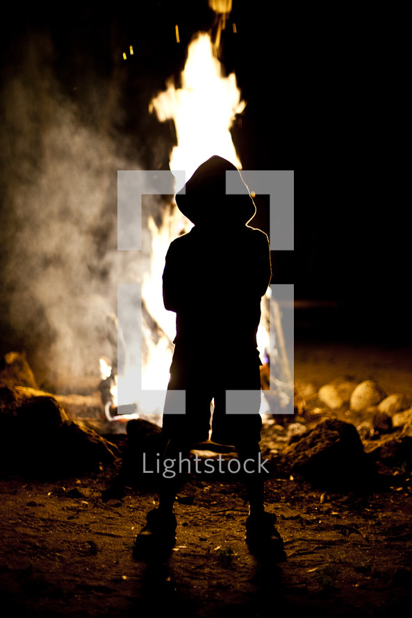 The silhouette of a hooded child standing in front of a fire