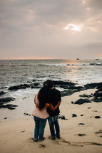 a couple standing on a beach hugging at sunset