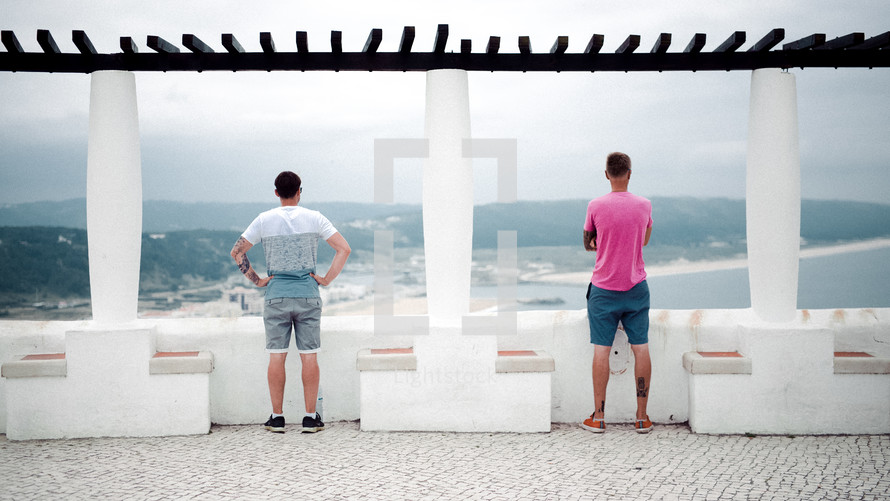 two men looking out at ocean waves