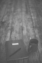 A pen and notebook next to a coffee mug on a wooden table