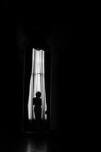 Silhouette of a woman in front of a tall curtained window.