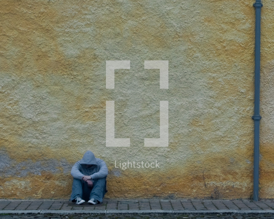 man in a hoodie sitting on a brick sidewalk with his head down