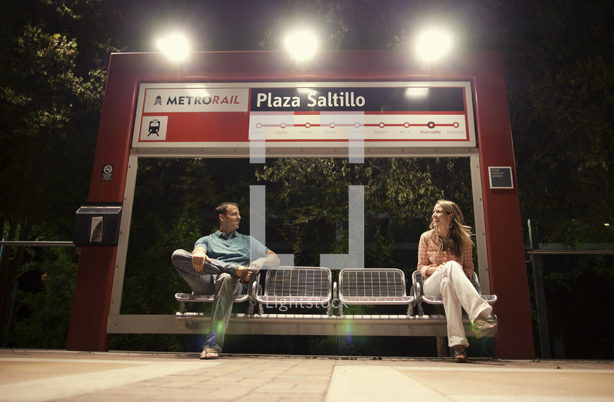 man and woman waiting at a metrorail stop