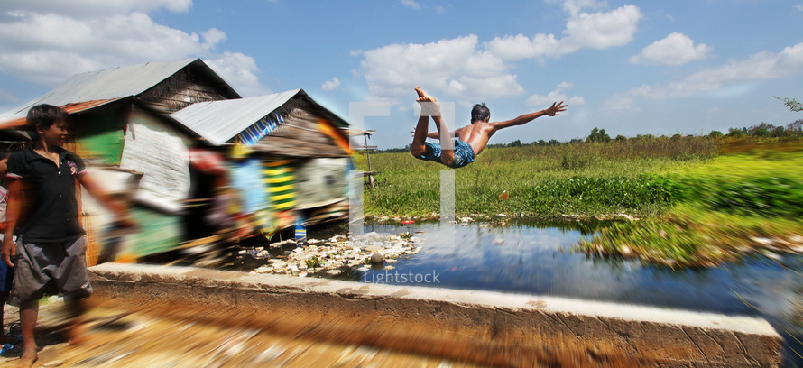 A young boy jumps and dives into a flooded river.
