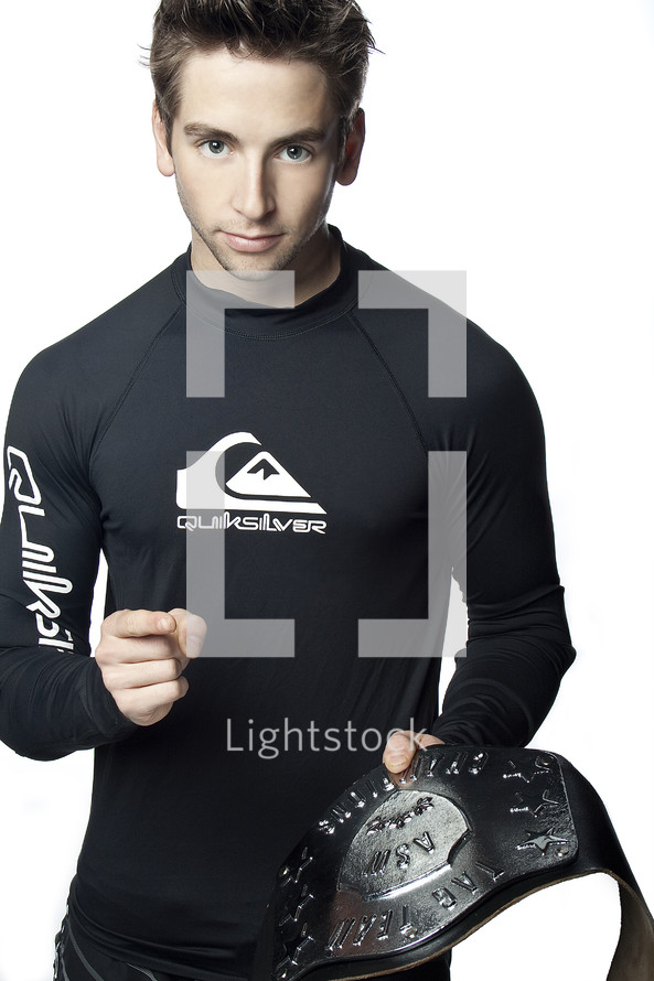 Champion; man in black rash guard holding a championship belt, pointing towards the camera.