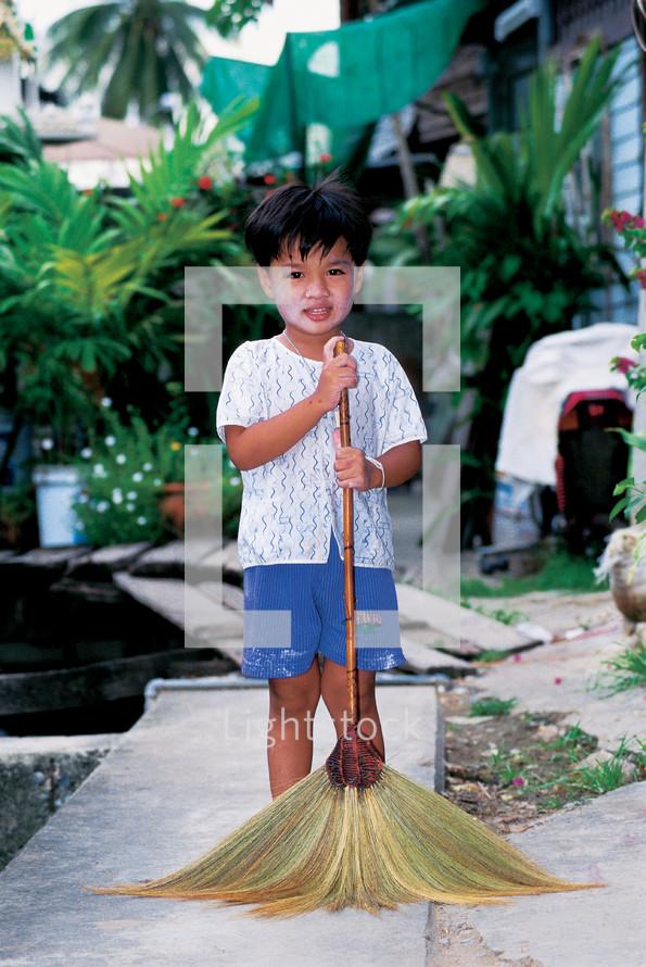 little Thai boy with a broom