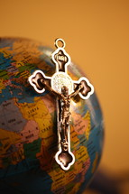 silver crucifix on a globe