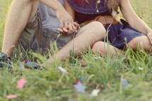 couple holding hands lying in the grass