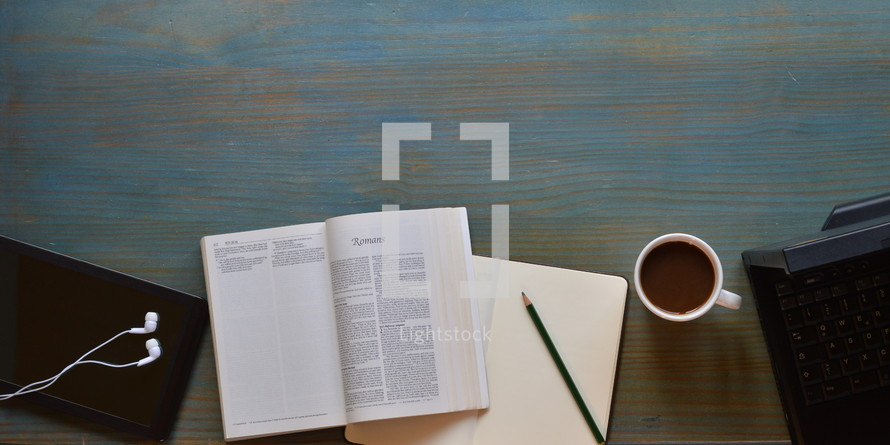 modern bible study of Romans with technology and a cup of coffee