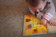 A baby pointing to Jesus in her children's picture Bible.