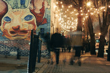 pedestrians walking down a city sidewalk at night and cat mural