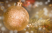 gold glittery ornament on a Christmas tree