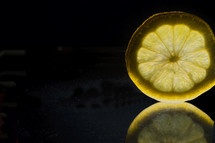 Slice of lemon with reflection.