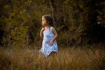 toddler girl standing in tall grass