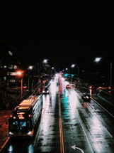 public bus on wet roads at night