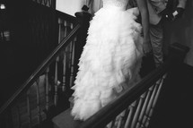 torso of a bride and groom walking down stairs