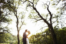 couple kissing under the trees