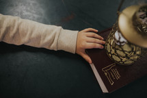 a child's hand on a Book and lantern