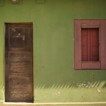 wood door and window on a green exterior wall