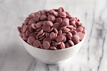 bowl of Authentic Ruby Chocolate Drops on a Marble Counter