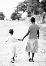 woman and girl holding hands and walking on a dirt road