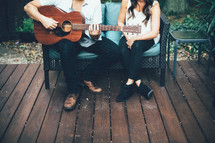 couple sitting on a bench and a man playing a guitar