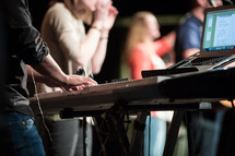 man at a soundboard on people on stage